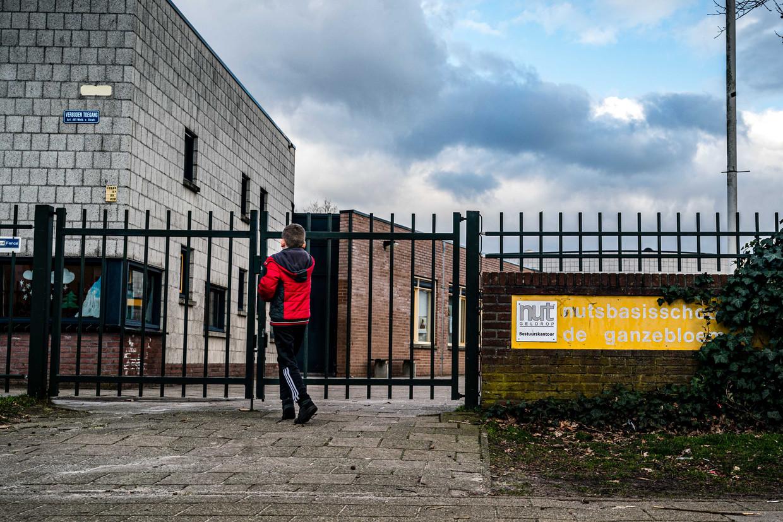 Een leerling voor het hek van de gesloten basisschool de Ganzenbloem. Beeld ANP