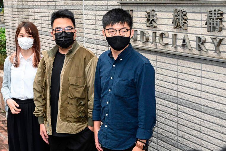 Agnes Chow, Ivan Lam en Joshua Wong bij de rechtbank in Hongkong.  Beeld AFP