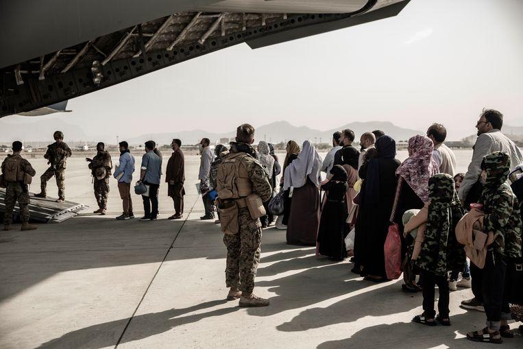 Mensen worden door Amerikaanse troepen begeleid bij het instappen van een militair toestel tijdens de evacuatie vanuit Kaboel.  Beeld AP