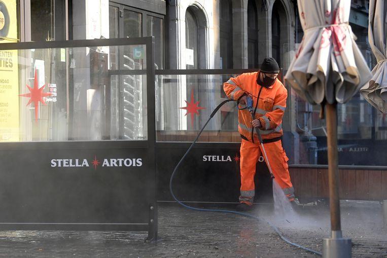 De Leuvense Oude Markt wordt schoongemaakt, in aanloop naar de verwachte heropening van de terrassen op 8 mei. Beeld Photo News
