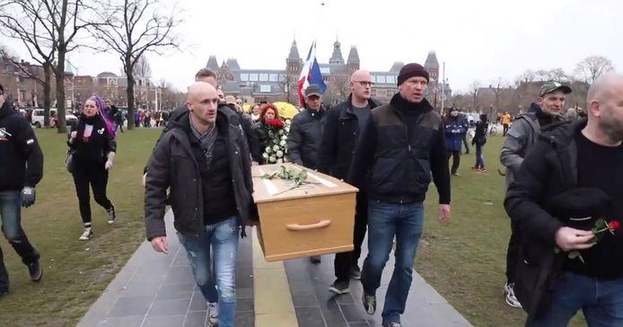 Betogers lopen met doodskist Museumplein op