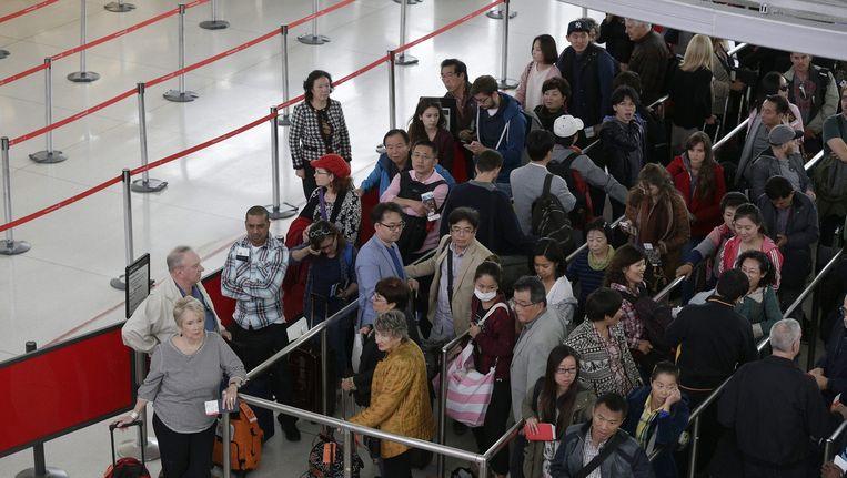 Reizigers wachten op hun controle op John F. Kennedy Airport Beeld epa