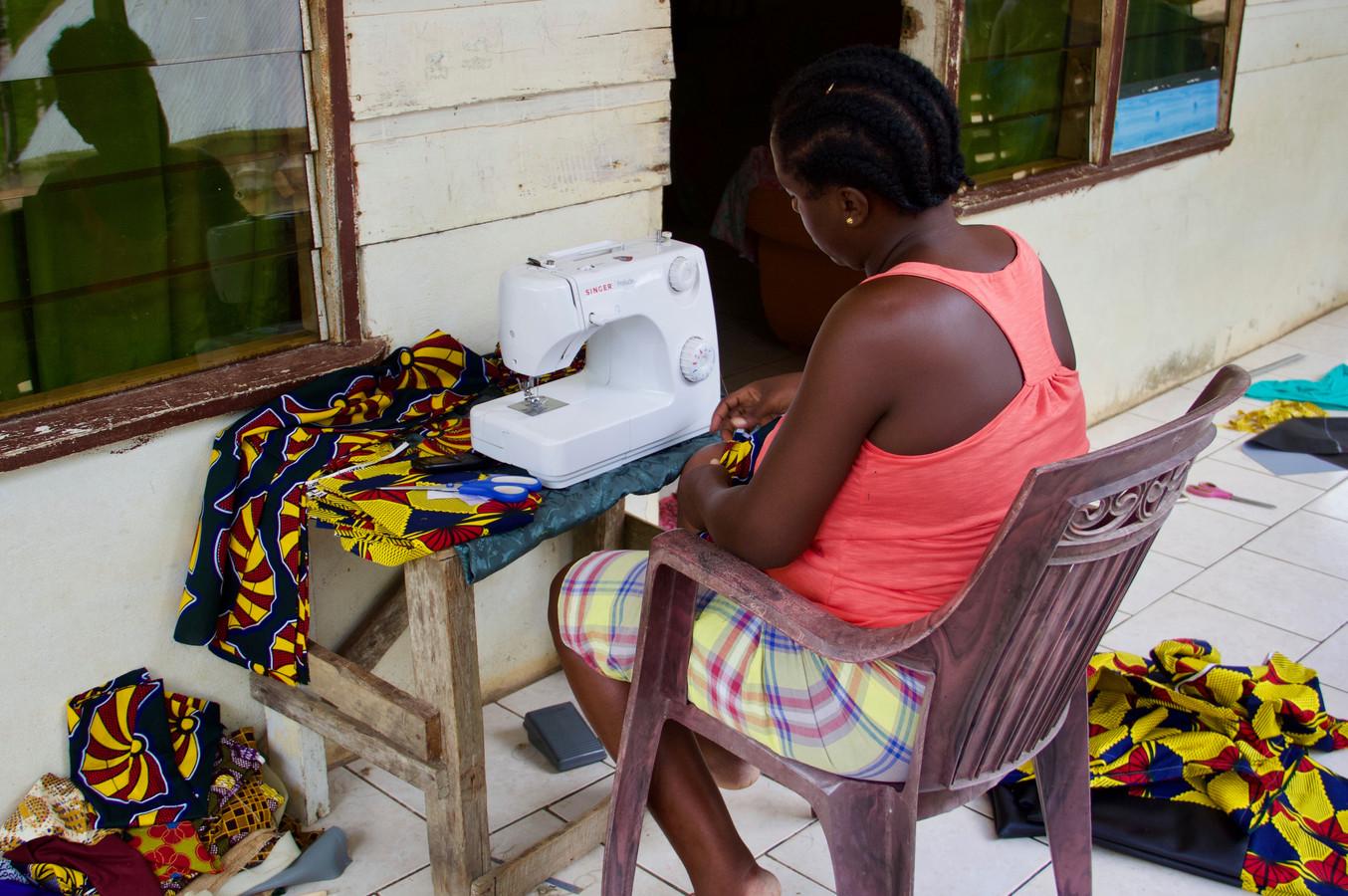 Stof met vrolijke print wordt bewerkt door een van de vrouwen