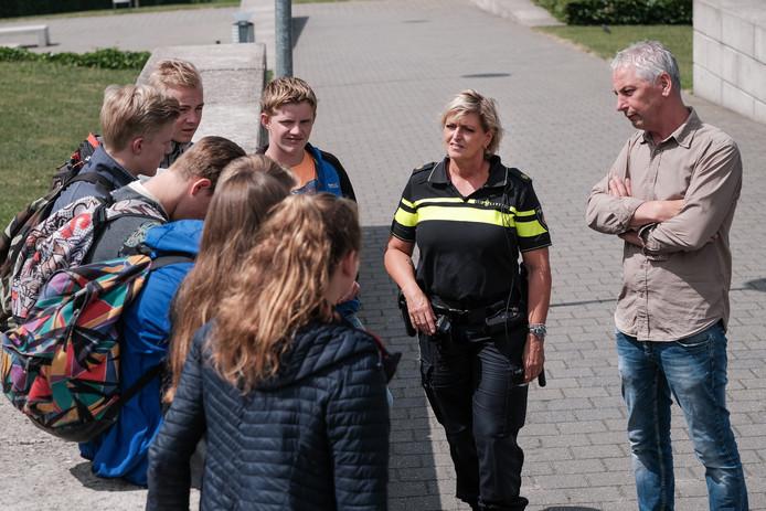 Schoolwijkagent Ellen van der Meulen en, rechts van haar, veiligheidscoördinator Willem te Kampe van het Metzo College, in gesprek met enkele leerlingen van het Metzo.
