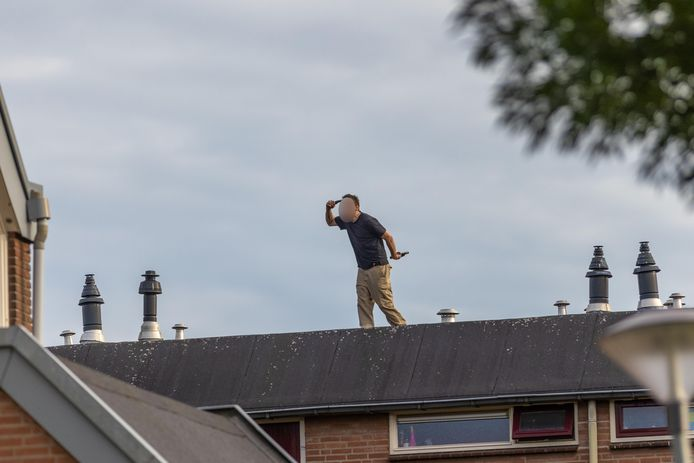 Rico P.  staat met vuurwapens op het dak van een woning in Huissen.