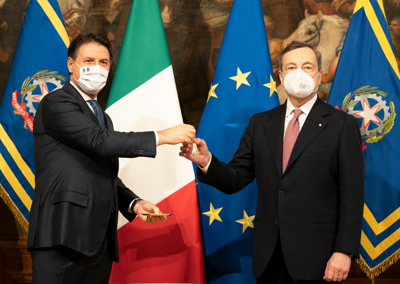 Vertrekkend premier Giuseppe Conte (links) geeft een belletje aan zijn opvolger Mario Draghi, als symbool voor de overdracht van de Italiaanse regering. Beeld EPA