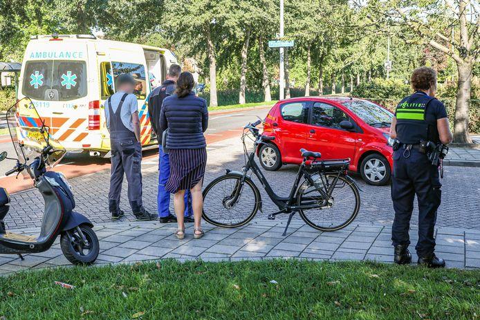 De e-bike staat met een gebogen voorwiel op de standaard terwijl de eigenaar ervan in de ambulance wordt verzorgd.