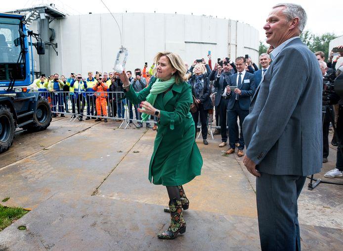 De nieuwe rioolwaterzuivering is officieel geopend. Minister Cora van Nieuwenhuizen gooit een fles water tegen een van de nieuwe bassins.