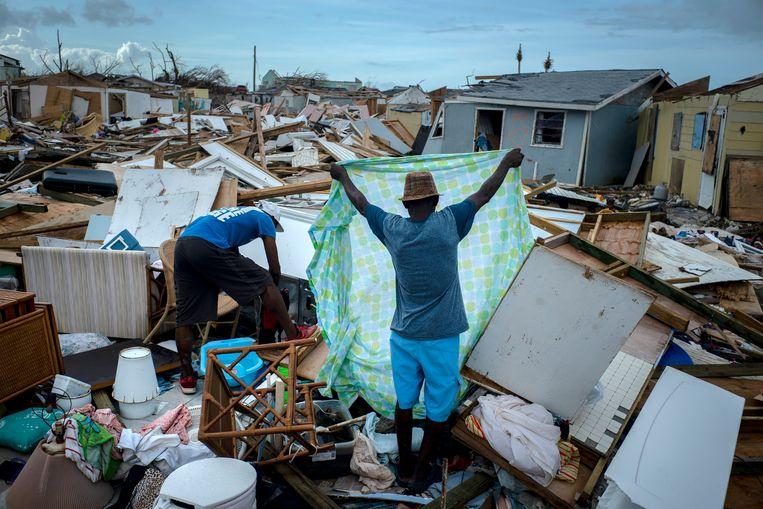 Mensen zoeken op de Bahama's hun eigendommen bijeen na de orkaan Dorian die in 2019 woedde. Volgens Oxfam Novib lopen arme 'klimaat-kwetsbare' landen rond 75 miljard dollar mis doordat rijke landen hun financiële beloftes niet nakomen. Beeld AP