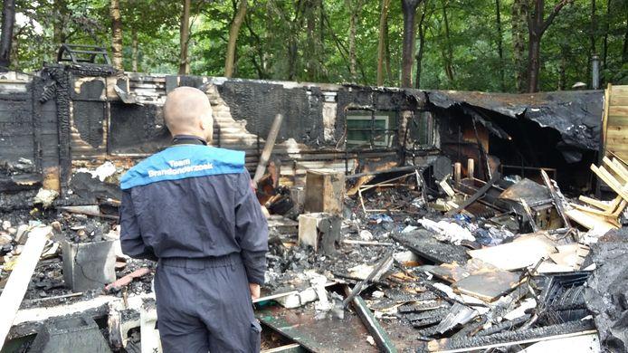 De brandweer doet onderzoek naar de oorzaak van de brand in het chalet.