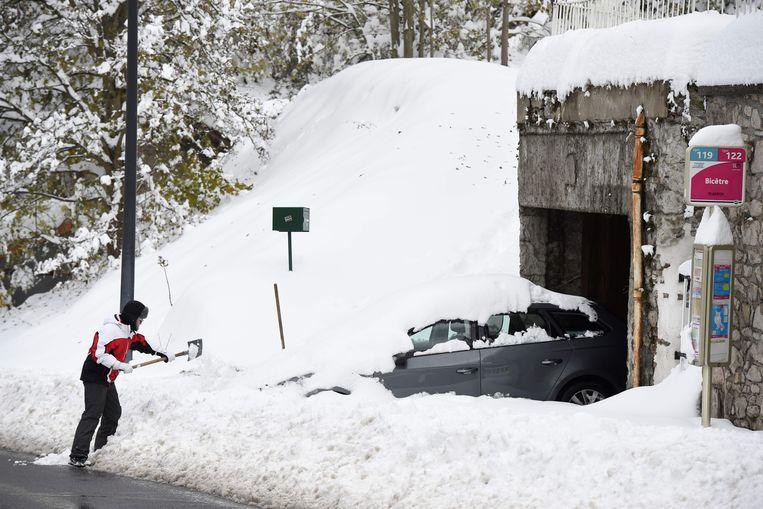 Een man probeert zijn auto uit de sneeuw te halen in Firminy in de Haute Loire in Frankrijk. Beeld AFP