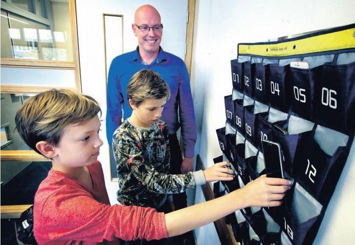 Soms zijn mobieltjes nuttig in de klas, vaak ongewenst. Op sommige scholen laten leerlingen ze achter in een soort wandtapijt.