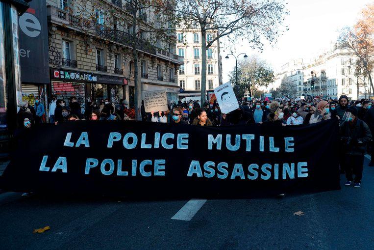 Demonstranten op het Place de la Republique in Parijs met een spandoek met de tekst: 'De politie verminkt, de politie vemoordt'. Beeld AFP