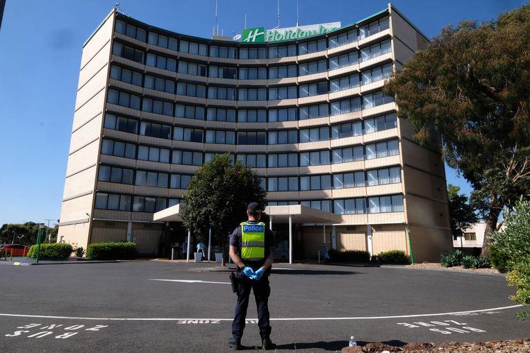 Een agent staat op wacht bij een quarantainehotel in Melbourne, Australië. Beeld EPA
