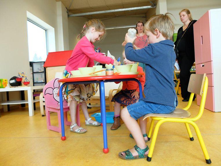 Deze kinderen testen het speelgoed in hun nieuwe klas al meteen uit.