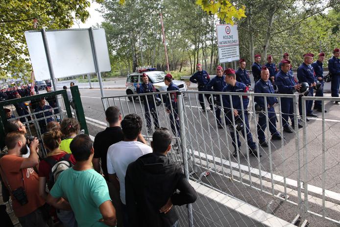 Vluchtelingen in september 2015 bij de grens tussen Servië en Hongarije. Hongarije laat ze niet door.