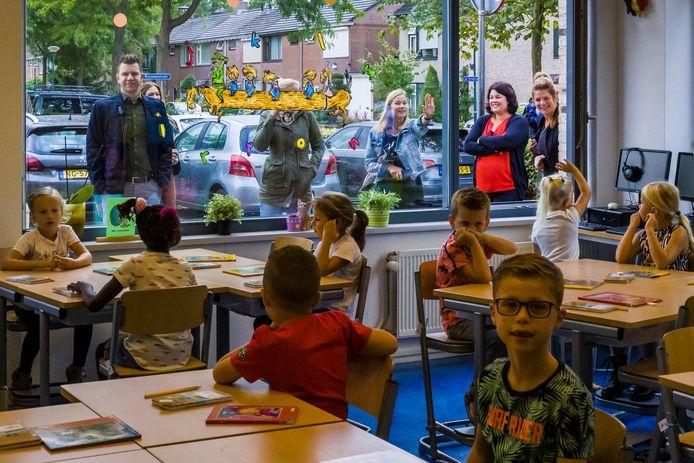 De ouders van groep 3 van basisschoole de Bussel nemen afscheid van hun kinderen op de eerste schooldag. De ramen staan open zodat er volop frisse lucht naar binnen kan.