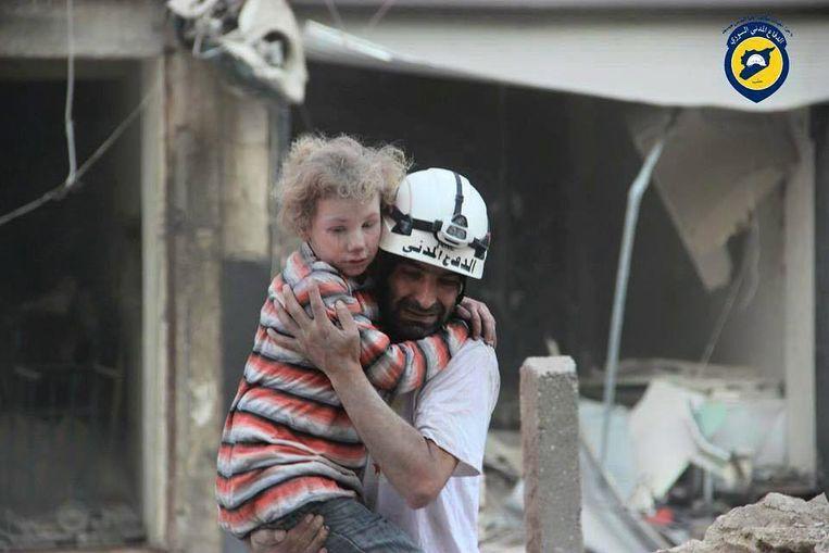 Archiefbeeld van een lid van de Syrische burgerbeschermingsbeweging Witte Helmen in actie in Aleppo. Het gaat om hulpverleners die gespecialiseerd zijn in de evacuatie van mensen vanonder het puin van gebouwen vernietigd door het Syrische leger of de Russische luchtmacht. Ze worden bedreigd met opsluiting of executie. Beeld EPA