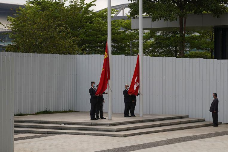 Overheidsfunctionarissen hijsen de vlag van China en Hongkong.  Beeld REUTERS