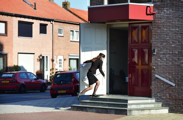 Een gelovige sluit de deur van de kerk van De Eben-Haëzerkerk in Urk. Beeld Marcel van den Bergh
