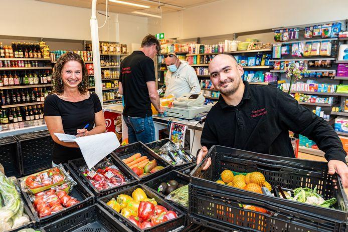 De minisupermarkt in Zwammerdam is wegens succes verhuisd naar een ruimere locatie. Linda en Cris (r) vullen samen de voorraden aan, terwijl Marc een klant helpt.