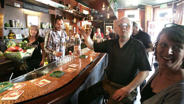 Eigenaar Tonne van Hateren (tweede van links) tapt een biertje. De rechtbank in Breda sprak cafe Victoria eerder vrij van overtreding van het rookverbod. Beeld ANP