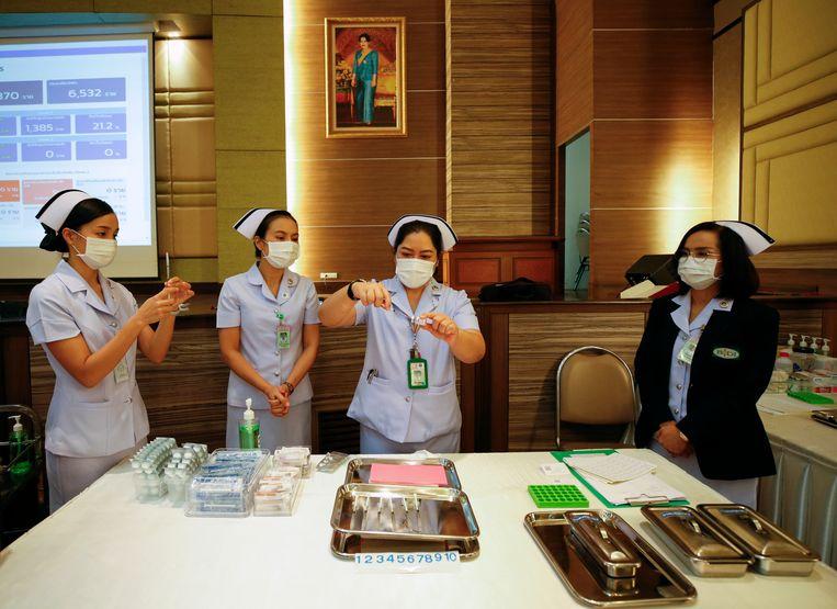 Een verpleegster in Thailand prepareert een spuit met het AstraZeneca-vaccin. Beeld EPA