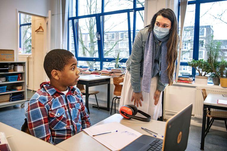 Zij-instromer Maartje helpt een jongen uit groep 6 met zijn schoolwerk. Beeld Guus Dubbelman / de Volkskrant