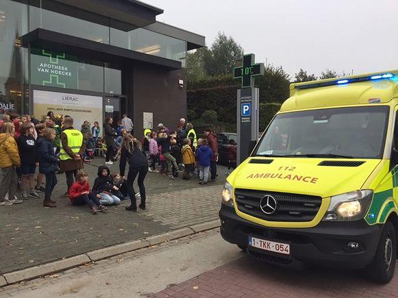 De kinderen verzamelden op de parking van de apotheek.
