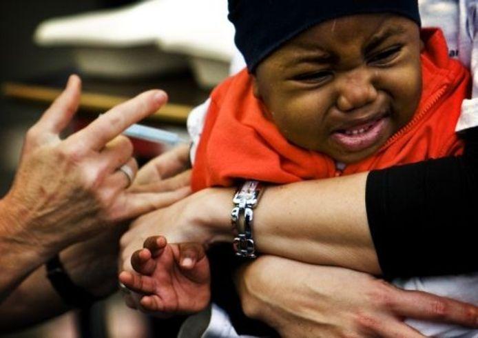 Een kind krijgt een prik tegen de Mexicaanse griep. ANP