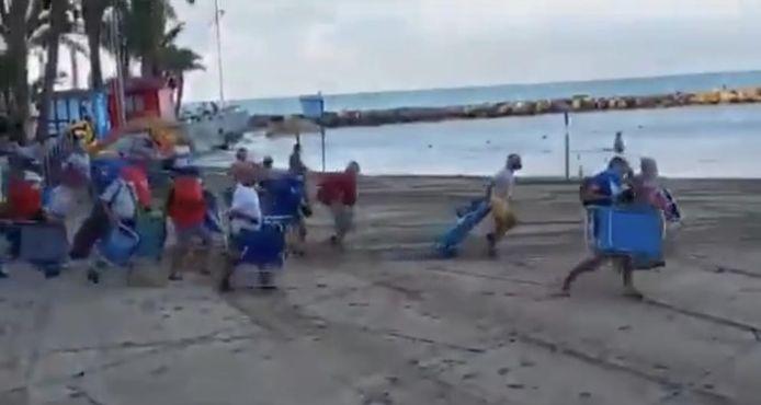 Met strandstoelen, parasols en frigoboxen rennen strandgangers naar het beste plekje.