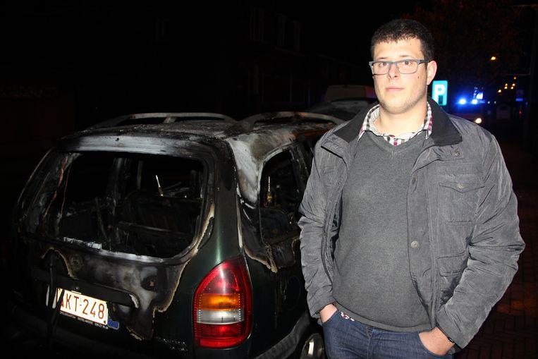 Jonas Coene (24) bij zijn uitgebrande wrak.