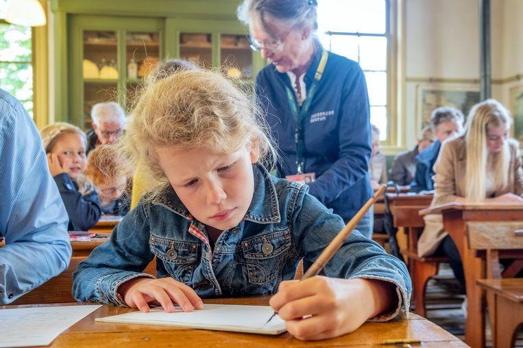 De linkshandige Martha Engberts leert de juiste pengreep om met een kroontjespen te schrijven. Beeld Patrick Post