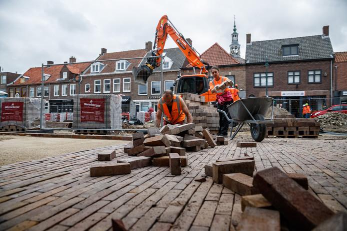 De eerste stenen van de nieuwe bestrating van het voetpad naast de nog open te graven haven in Zevenbergen worden gelegd.