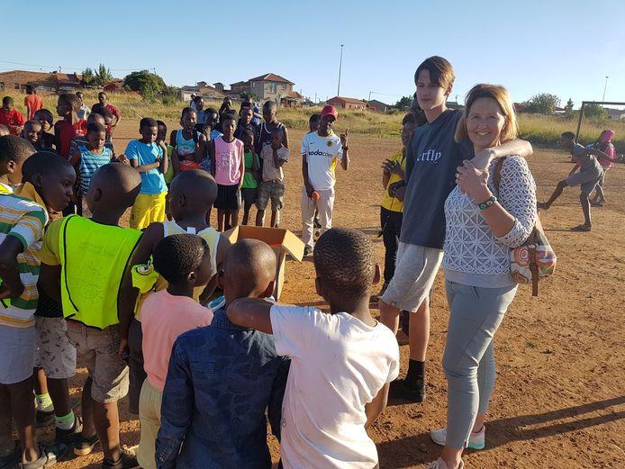 Samen met zijn moeder Antoinette deelt initiatiefnemer Stan Benneker van 'Kicks4Africa' voetbalschoenen uit aan Zuid Afrikaanse kinderen in een buitenwijk van Johannesburg.