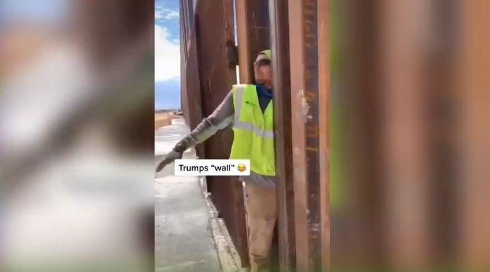 Un ouvrier passe entre les barreaux du mur de Trump.