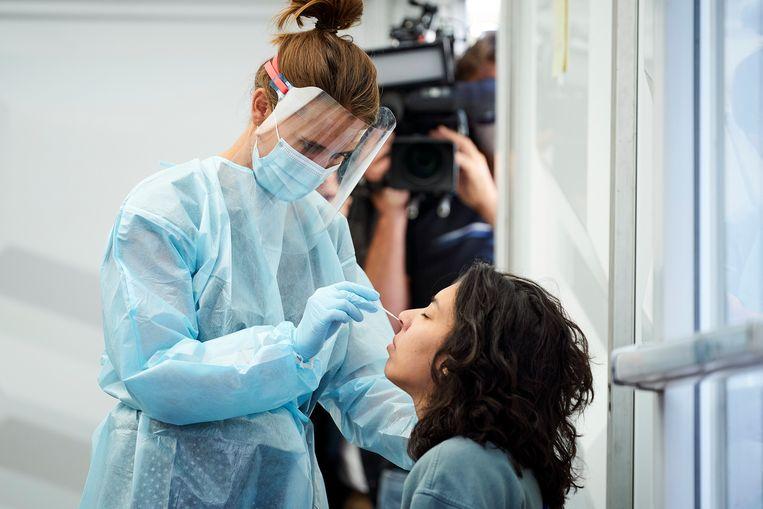 Een GGD-medewerker neemt een test af bij iemand met klachten. Beeld Phil Nijhuis