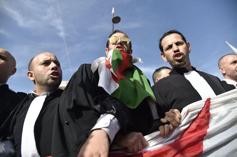 Algerijnse vlaggen en boze gezichten tijdens de demonstraties in hoofdstad Algiers, al verloopt alles voorlopig vreedzaam. Beeld AFP