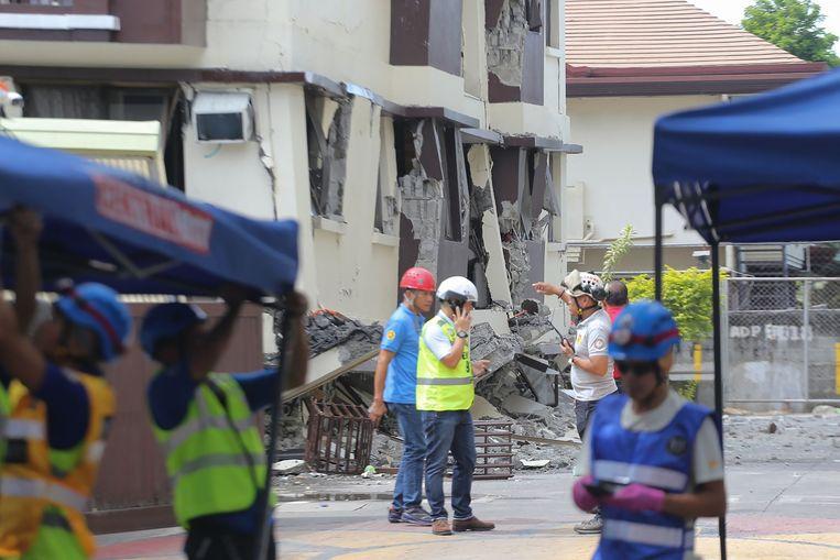 Arbeiders inspecteren ingestorte gebouwen in Davao City op het zuidelijke Filipijnse eiland Mindanao. Beeld AFP