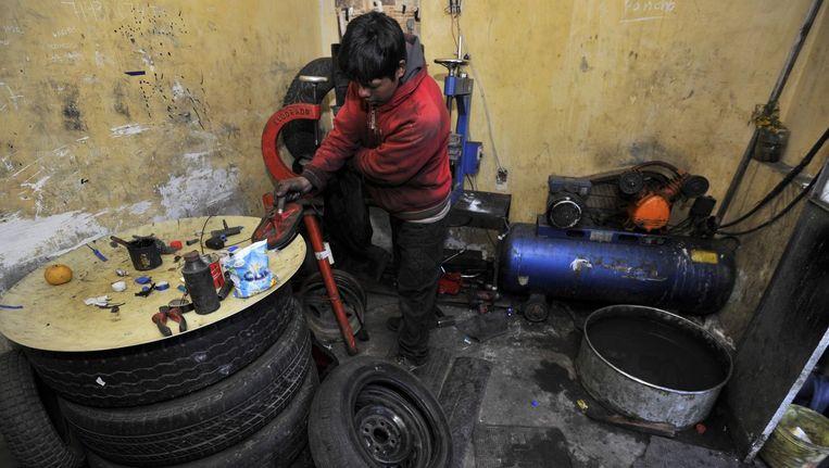 Een jongen repareert banden in de Boliviaanse hoofdstad La Paz. Beeld anp