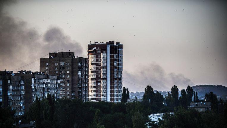 Rookpluimen boven Donetsk op 27 juli. Beeld afp