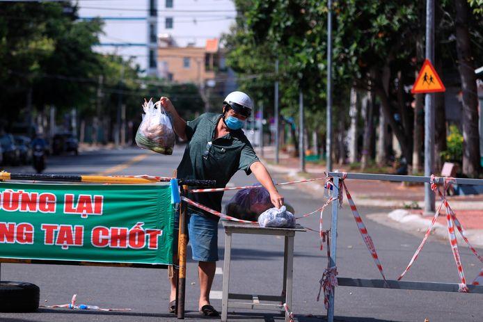Een bezorger laat bestelde groenten en fruit achter in de kuststad Vung Tau. In Vietnam zijn momenteel lockdownmaatregelen van kracht.