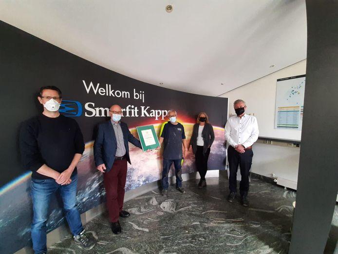 Medewerkers van de Eindhovense kartonfabriek krijgen de oorkonde overhandigd.