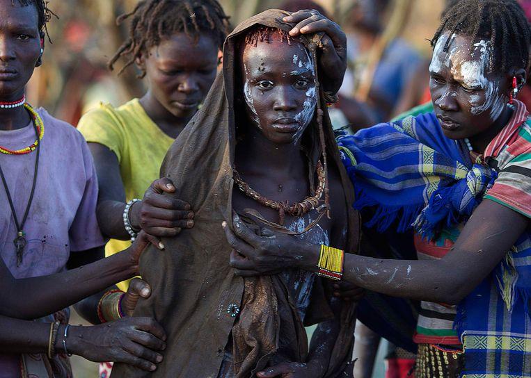 Een Pokotmeisje in Kenia, ceremonieel gehuld in dierenvellen, op weg naar een rustplaats na haar besnijdenis – een rite de passage binnen haar stam. Beeld Reuters