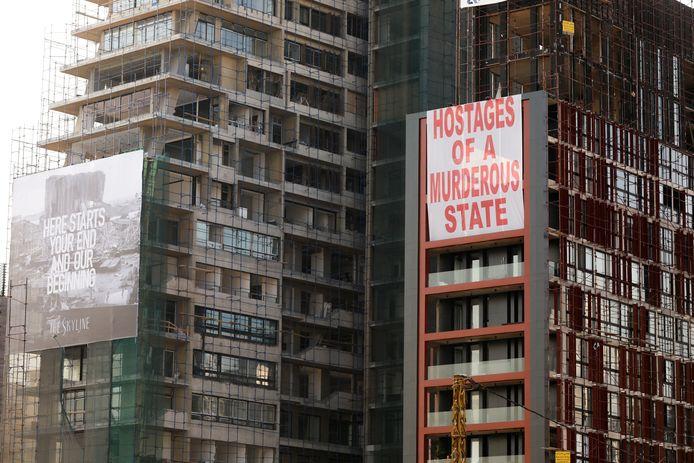 Spandoeken met de tekst 'Hier begint jouw einde en ons begin' en 'Gijzelaars van een moorddadige staat' hangen aan een gebouw dat beschadigd raakte door de explosie.