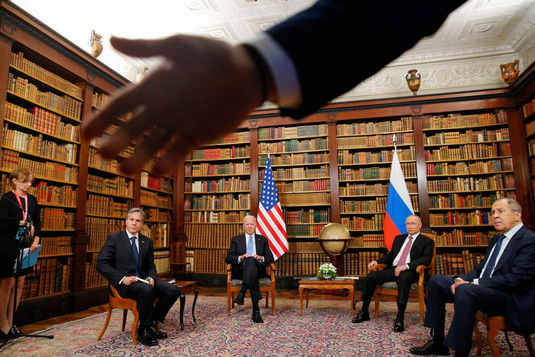 Een veiligheidsfunctionaris bij de topontmoeting tussen de presidenten Biden en Poetin, in Genève afgelopen woensdag, geeft fotojournalisten met een handgebaar te kennen dat zij een stap naar achteren moeten doen.  Beeld AP
