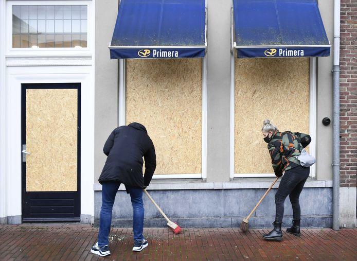 Bosschenaren ruimen de rotzooi op bij de Primera-winkel in de ochtend na de avondklokrellen.