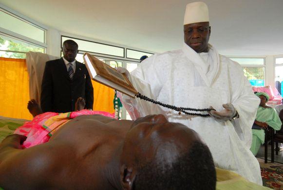 Yahya Jammeh gaat er prat op dat hij tientallen aidspatiënten heeft genezen van de dodelijke ziekte. Hier voert hij een 'genezend ritueel' uit op een aidspatiënt. Foto uit 2007.
