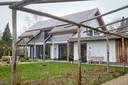 De pergola van kastanjehout en op het huis zonnepanelen en zonneschermen.