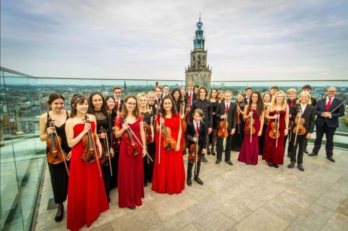 Het Haydn Jeugd Strijkorkest met op de achtergrond de Groninger Martinitoren.